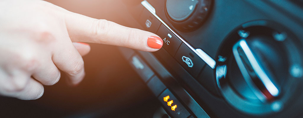 Woman turning on air conditioning in car
